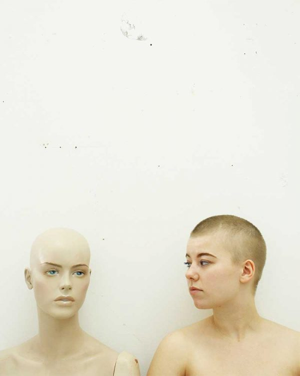 Lara Usherwood - Image of a female model with a shaved head looking at the head and shoulders of a mannequin in front of a white walll