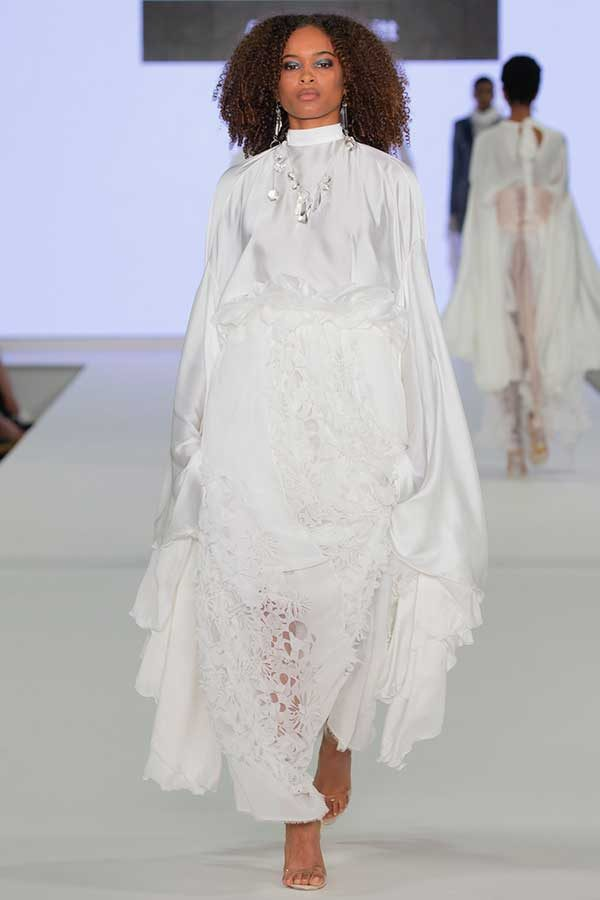 Amelia Nevitt - Image of a model wearing and white dress with detailed lace and draping