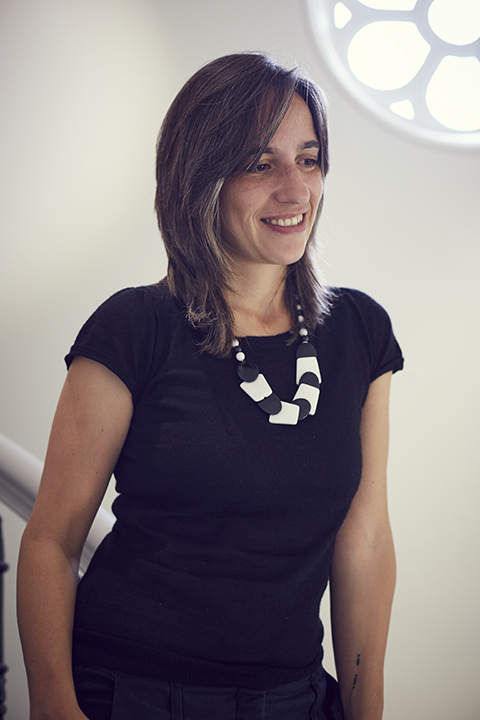 portrait photo of lecturer doctor Ana Rute Da Costa standing with arms by side and smiling away from camera with medium brown hair and a black t-shirt