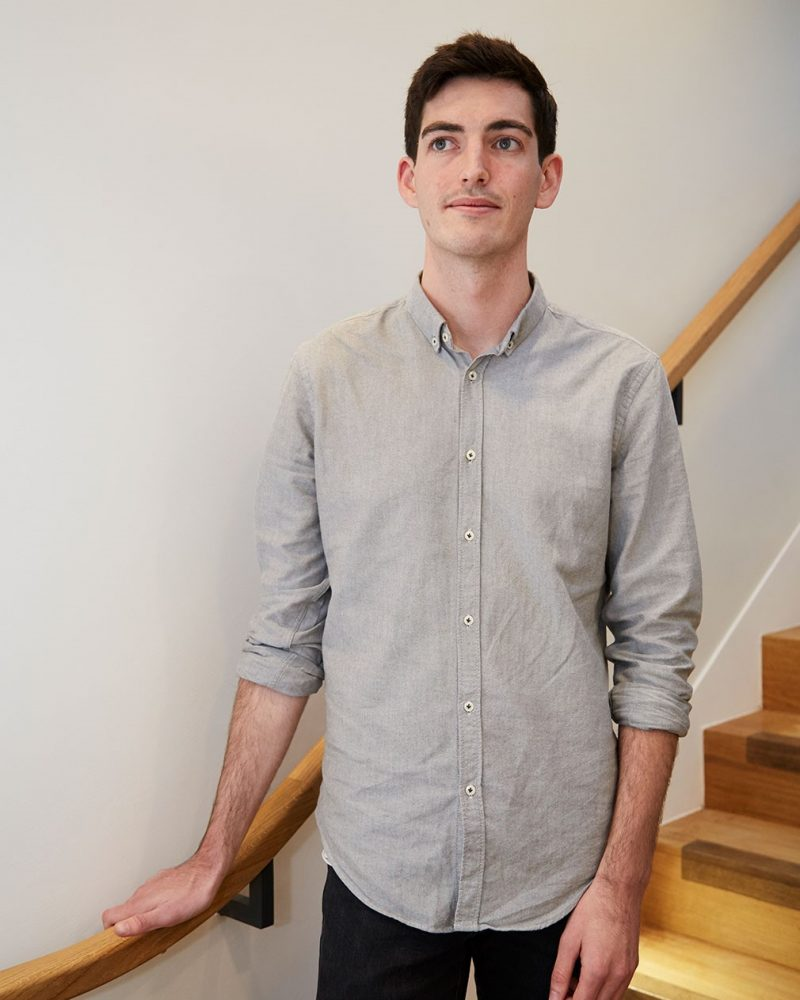 photo of alum Laurence Berry looking away from camera and standing next to staircase railing with short dark hair wearing loose grey shirt with rolled sleeves
