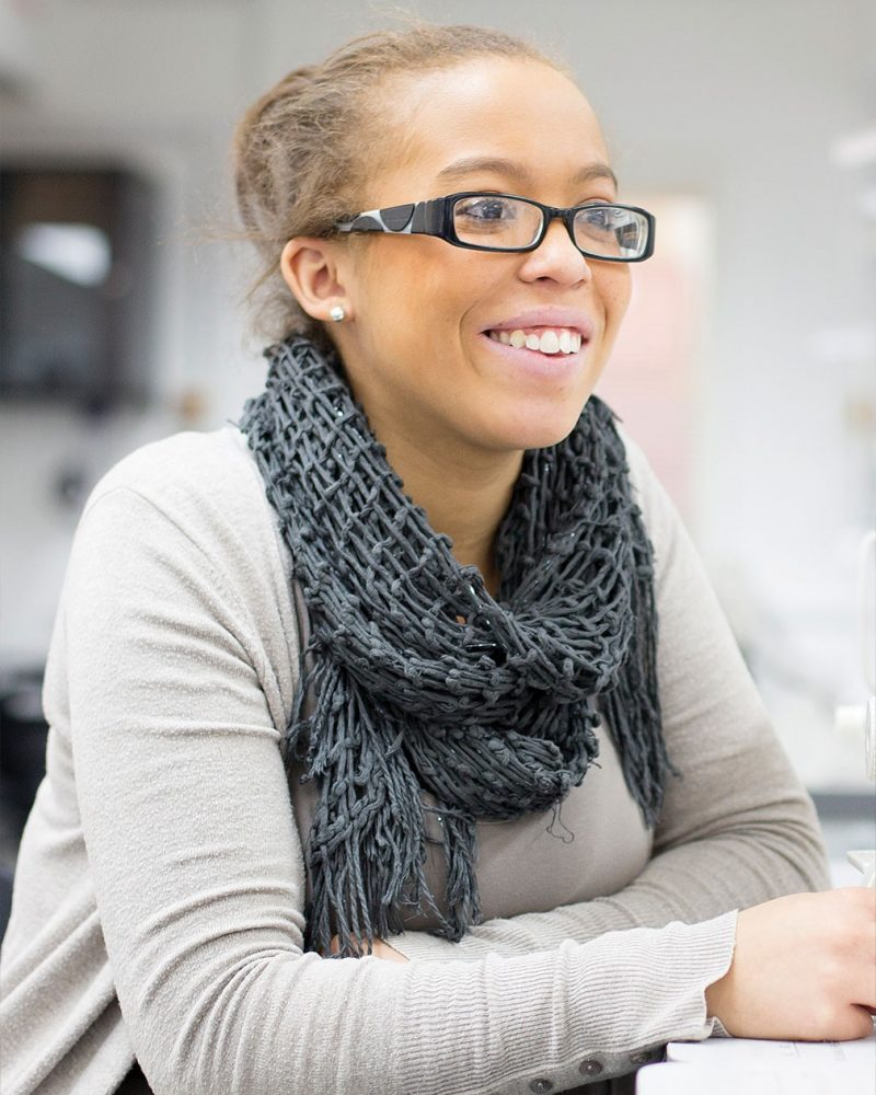 portrait photo of alum Chana Watson sitting at a desk, looking away from camera and smiling with tied back hair, glasses, a loose knit scarf and a long sleeved top