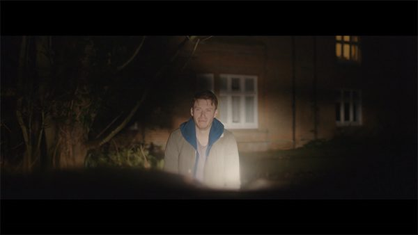 Amnesiac - screenshot from film by Alex Hermon shows a man standing outside of a house lit by the headlights of a car with an upset look on his face and staring towards the camera which is set in the car