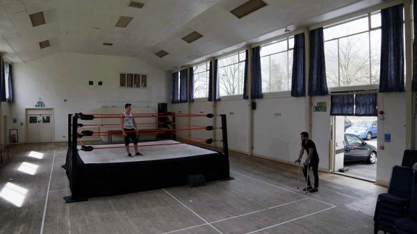 Hitting the Mat - screenshot from film by Alexander Dimmock shows a wide shot of a gym hall during the day with high wide windows and a man walking in through a set of doors in crutches with another man standing in a boxing ring in the center looking at the other man