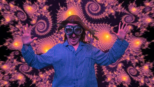 Mr 8 Billion - screenshot from film by James Taylor shows a person wearing blue and white striped baggy pyjamas with open hands raised and aviation goggles on face with long brown hair against bright background of swirling shapes in purple and yellow against a black background
