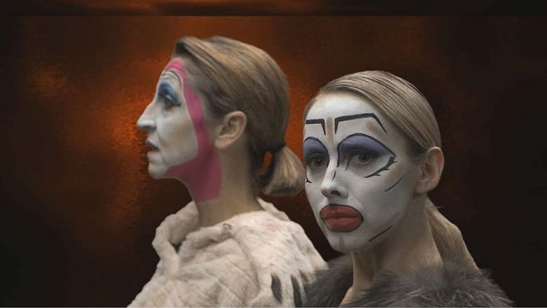 Red Hot - screenshot from film by Josh Dear shows a woman with head turned to camera in white facepaint with overdrawn black eyebrows, eyeshadow and lips with another woman standing behind and looking away with similar white facepaint but with a pink line around head to chin and fur coat