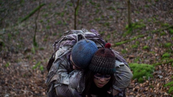 Crawl - Screenshot from student film by Thomas Evans depicts one person wearing a knitted bobble hat and scrappy clothing with painted face around eyes with another person slumped on back wearing similar scrappy clothing in woodland area