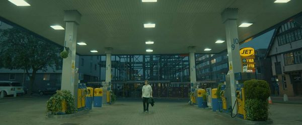 Finding Ferris - screenshot taken from film by Vivienne Warland shoes a man walking through a petrol station pumping with grey sky and fluorescent lights switched on wearing a white shirt and carrying a coat