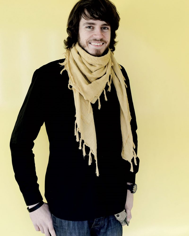 portrait photo of alum Simas Balciunas smiling at camera with medium black hair wearing a thin scarf with long sleeved dark top