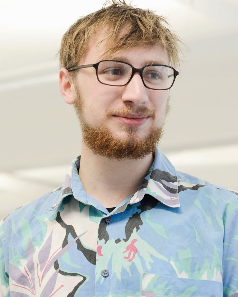 portrait photo of alum Alex Nicholson looking off screen with short spiky hair wearing glasses in a large print floral shirt