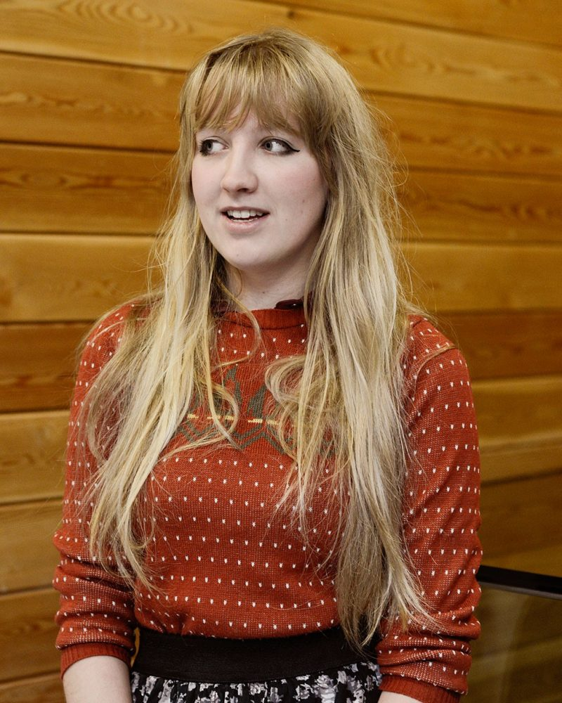 portrait photo of alum Charlotte Simpson smiling and looking off camera with long hair and a rolled sleeve top against wooden wall background