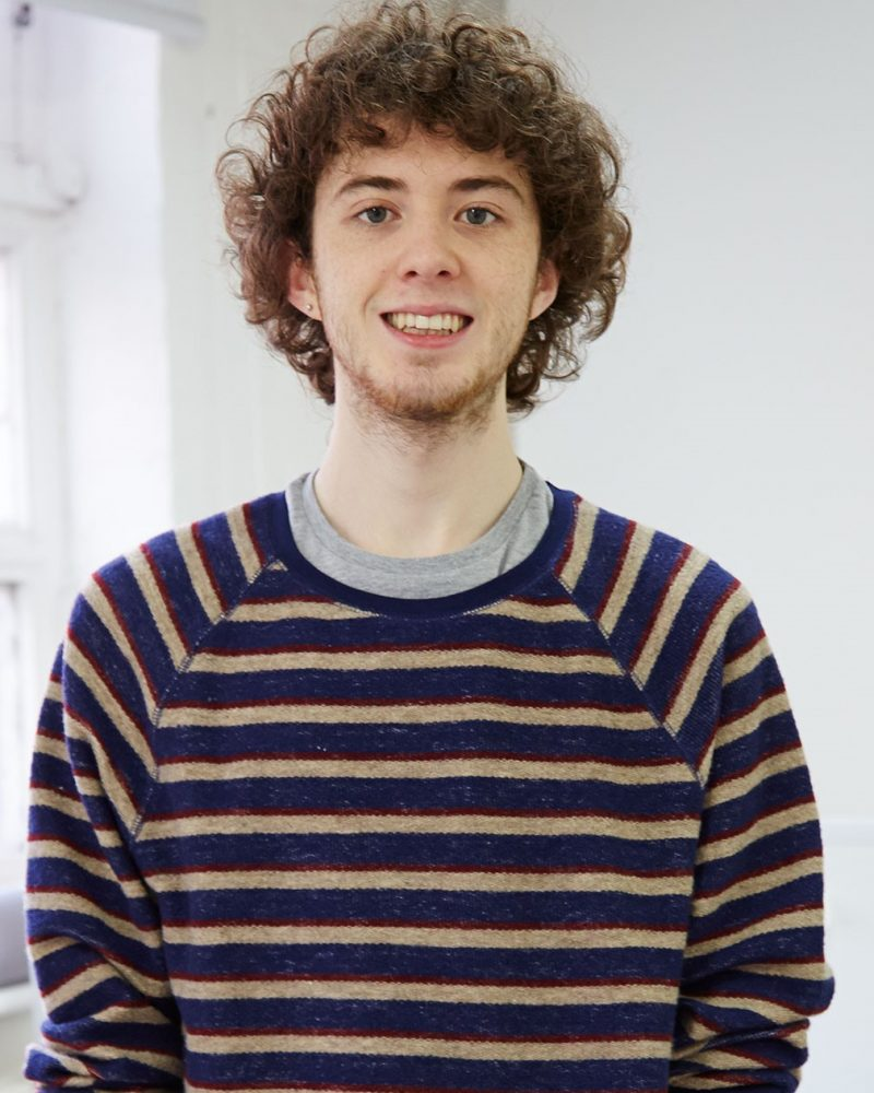 portrait photo of alum Michael Bartley smiling at camera with curly hair and blue and yellow striped jumper