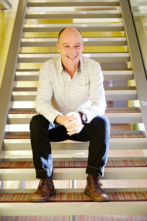 photo of course leader peter martin sitting on stairs and looking at camera while smiling and clutching hands with short hair and horizontal striped shirt
