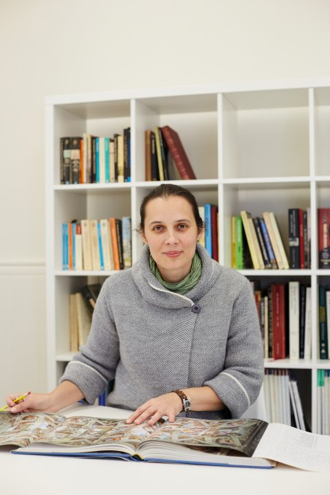 portrait photo of course leader Iuliana Gavril sitting at desk with hands on open book while looking at camera and smiling with tied back brown hair and buttoned grey knit jumper