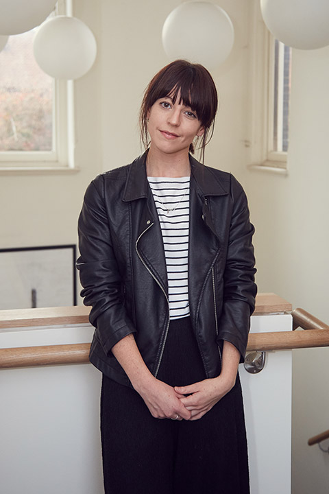 portrait photo of lecturer Kathryn Easthope leaning against wooden railing on white wall and looking at camera while smiling with tied back hair and open black leather jacket