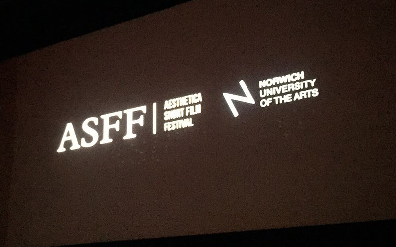 photo of a large cinema screen in dark room with the title A S F F and title for the Aesthetica Short Film Festival and an NUA logo