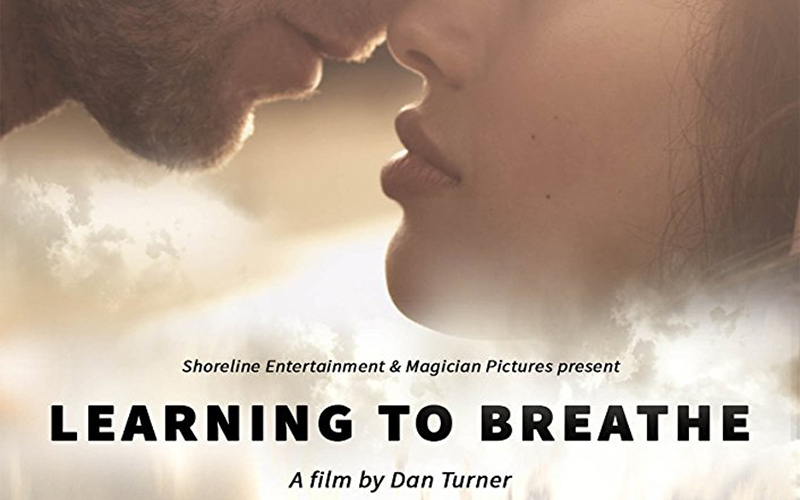 poster for senior lecturer Dan Turner's film Learning to Breathe shows a man and woman's face with lips close to each other bright and white background similar to clouds
