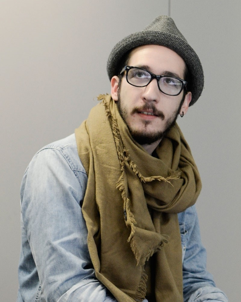 portrait photo of alum Adrian Ardelean looking away from camera wearing hat with glasses and loose khaki scarf and blue denim shirt