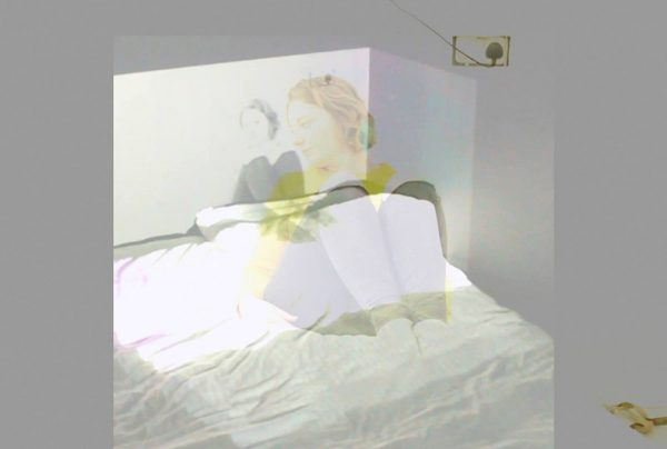 - edited photo with a faded overlay of woman sitting on bed and leaning against wall and looking over shoulder at a projection of a black and white photo