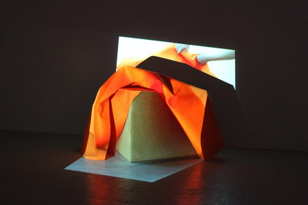 - photo of exhibition piece shows lit cube with orange fabric draped over the top and a projection showing hands manipulating the same cloth being played over it