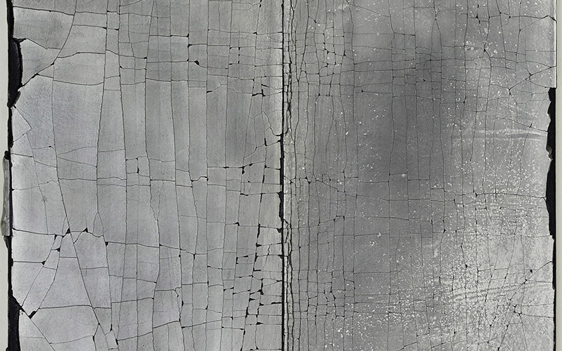 image shows cracked material in greyscale, highlighting the cubic fractures on a black background with smooth but faded surface type