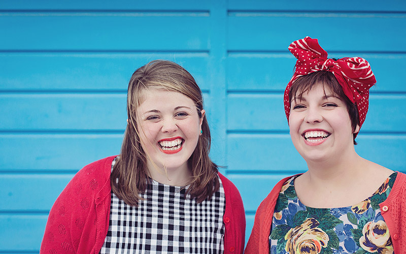 photo shows two women with beaming smiles looking at camera, one has medium brown hair and an open red cardigan and the other has red fabric tied around her head in a floral top against a blue fence background