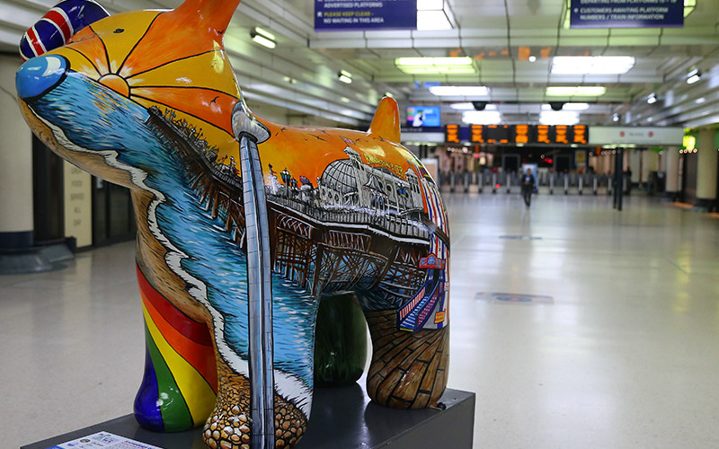 Photo of a dog statue mounted on short plinth in foreground covered in colourful illustrations of a pier with bright cartoon sun shining rays of light with a wide train station corridor and ticket checkpoint in background