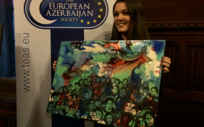 photo of alum Louisa Marriot shows a student holding a painting of vibrant colours with swirling shapes and black outlines of people painted on top of the colour base