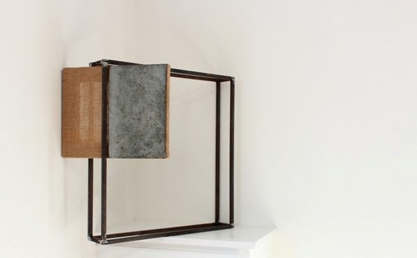 - photo of exhibit piece shows white wall with white table holding up a black metal cube frame with a split fabric and grey wood board suspending at an angle in one corner