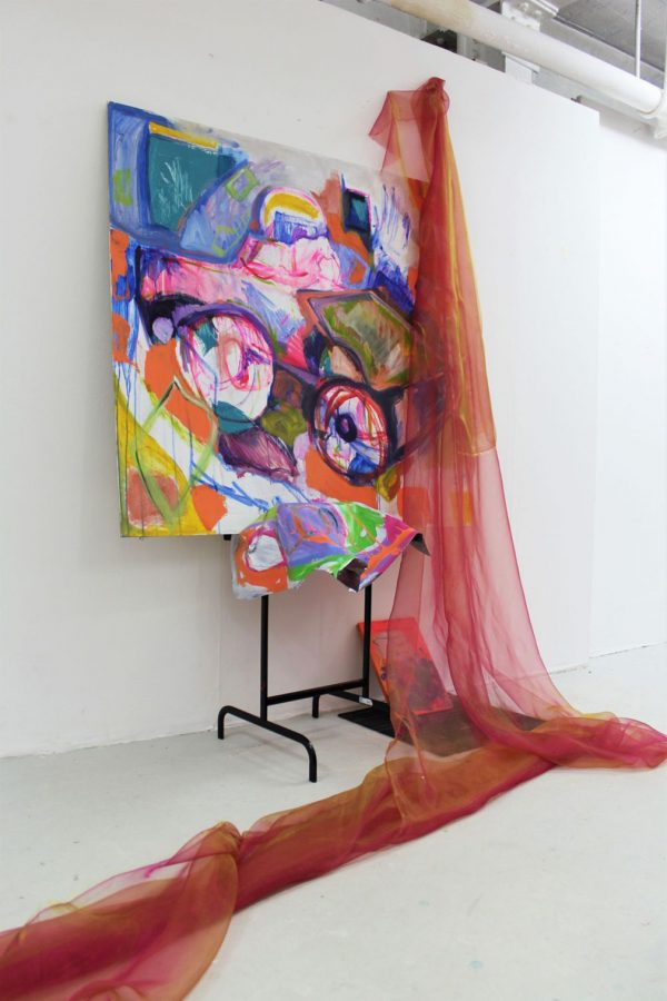 - photo of exhibition piece shows white wall and concerete floor with black metal stand and large abstract painting mounted with bright colours and non uniform shapes with long red transparent fabric pinned above and trailing to floor and off screen