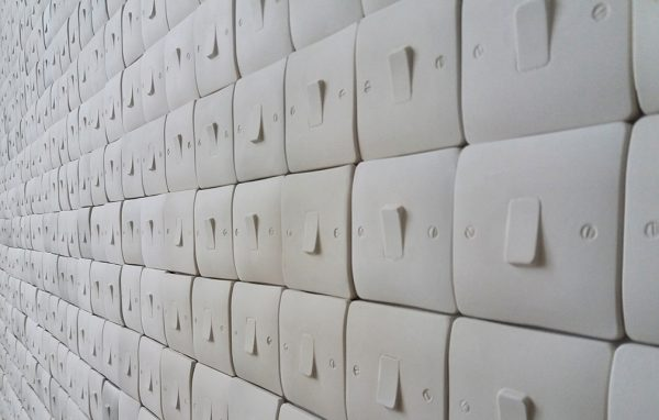 - image shows long wall of seemingly infinite light switches of the same type with no spacing and set randomly