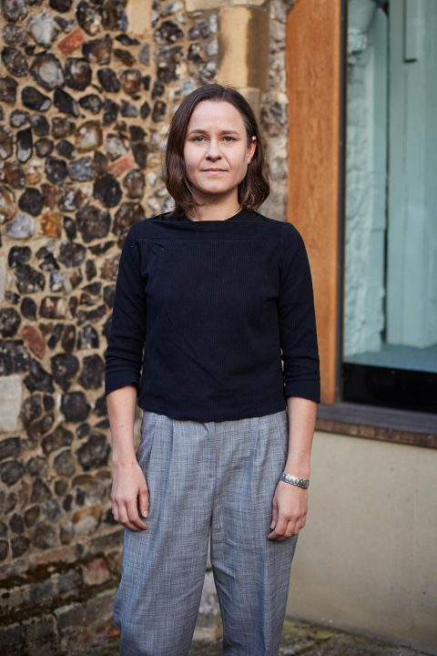 Portrait photo of lecturer Gretchen Geraets standing with arms by side and smiling at camera with medium brown hair and a rolled sleeved dark blue jumper