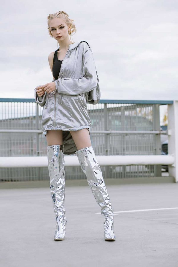Beth Poulter - Image of a model standing in an urban landscape wearing silver clothing