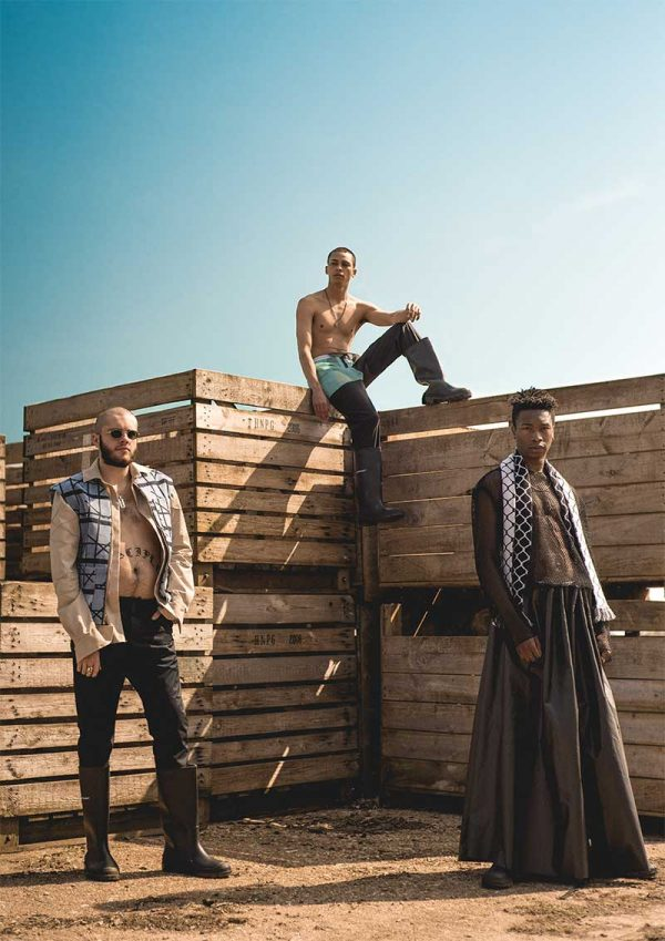 Caitlin Brown - Image of three male modesl looking to camera standing on a beach with wooden pallets behind them