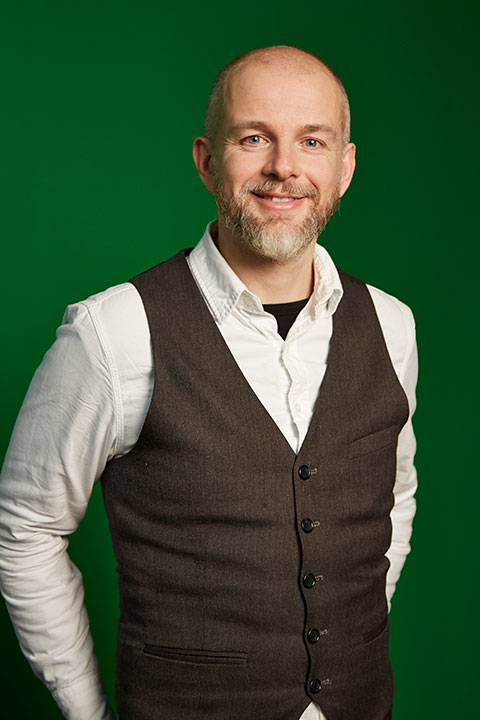 portrait photo of senior lecturer dan turner smiling at camera with short grey hair and a white long sleeved shirt with a dark grey waistcoat