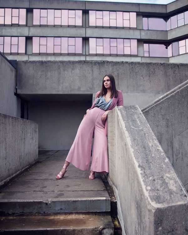 Egle Mykolaityte - Image of a model wearing a pink outfit standing in an urban landscape surrounded by concrete buildings