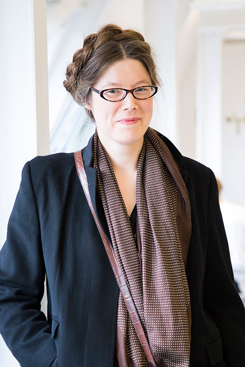 portrait photo of senior lecturer Emily Mitchell standing and smiling at camera with hands in pockets with brown braided hair and brown cat eye glasses and a red and white spotted scarf and an open suit jacket