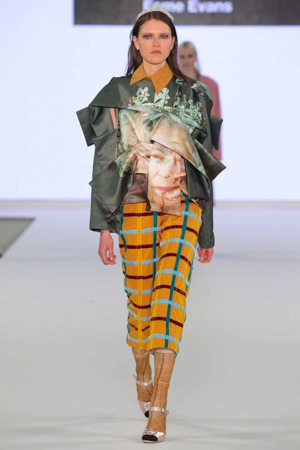 Esme Evans - Image a female model wearing a garment with the queens face on and yellow checked trousers