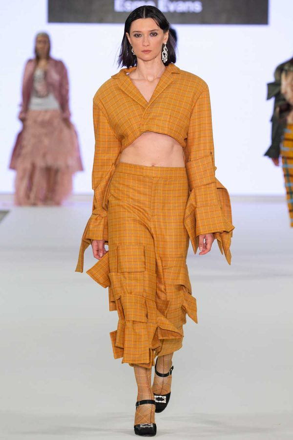 Esme Evans - Image of a model wearing a yellow garment on a catwalk