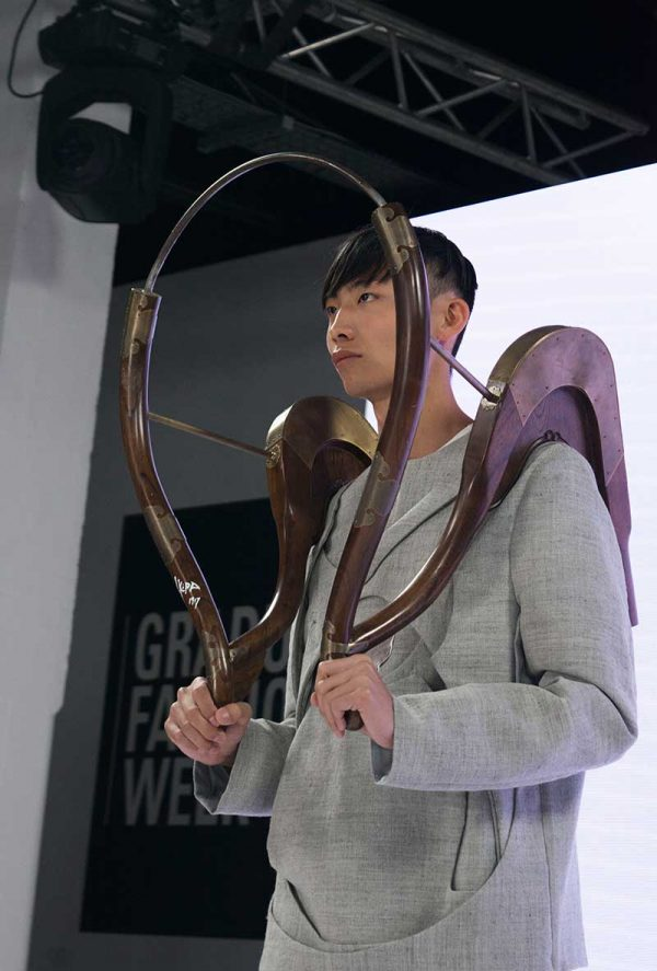 Bran Wan - Image of a model wearing a tailored garment with a wooden shoulder sculpture