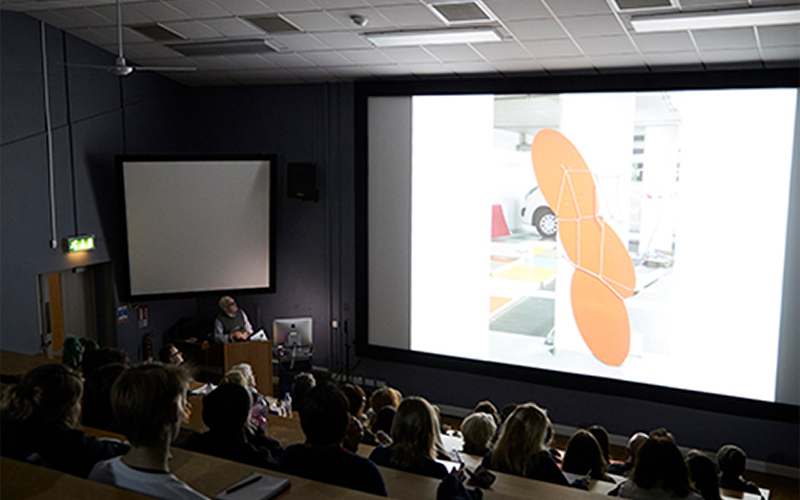 photo of NUA lecture theatre taken from the back of the room showing attendees sitting in graduated benches with a speaker looking at a projection screen showing a design on a white background