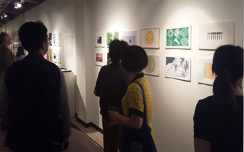 photo of an exhibition space shows a white wall with various printed work pinned to wall and attendees in foreground observing the work