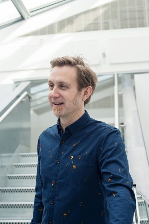 portrait photo of senior lecturer Glen Robinson standing and looking away from camera with short light brown hair and a long sleeved blue shirt yellow splash patterns