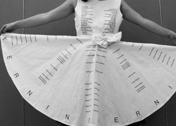 - Image of a girld holding a dress with the words Kerning printed on to the skirt