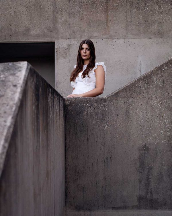 Gudbjorg Ylfa - Image of a model wearing a white dress standing amongst concrete buildings