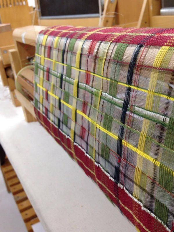 - photo of woven fabric created on a loom has thin under layer with with spaced green and yellow fibers woven in a large grid spacing