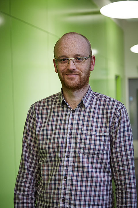 portrait photo of lecturer Jon Dunleavy standing with arms by side and smiling at camera with short red hair and a plaid white and red shirt