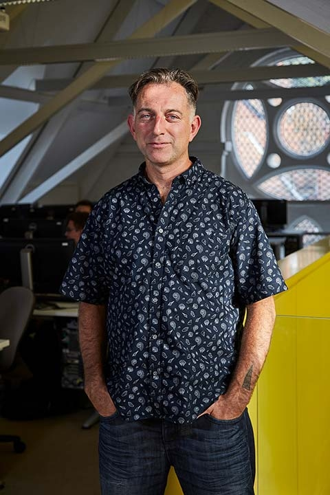photo of Lecturer Jamie Gledhill standing with hands in pockets and smiling at camera with short light brown hair and a loose patterned blue shirt