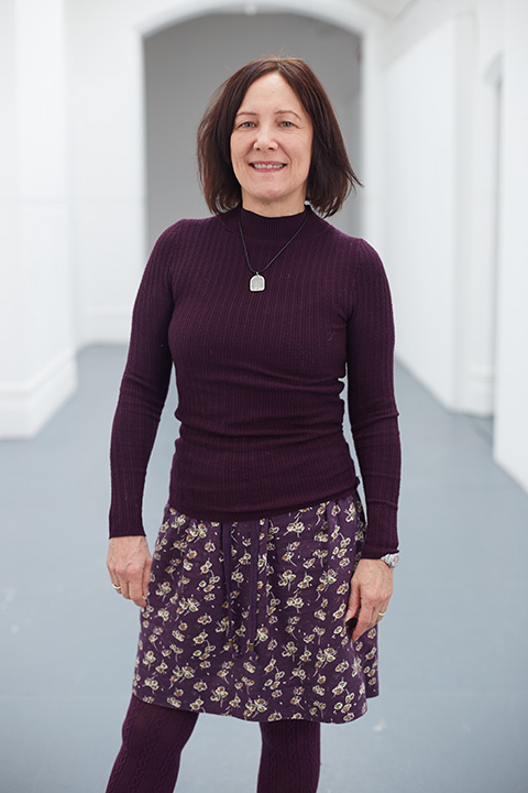 photo of Judith Schoch standing and smiling at camera with arms by side and medium brown hair with purple long sleeved jumper