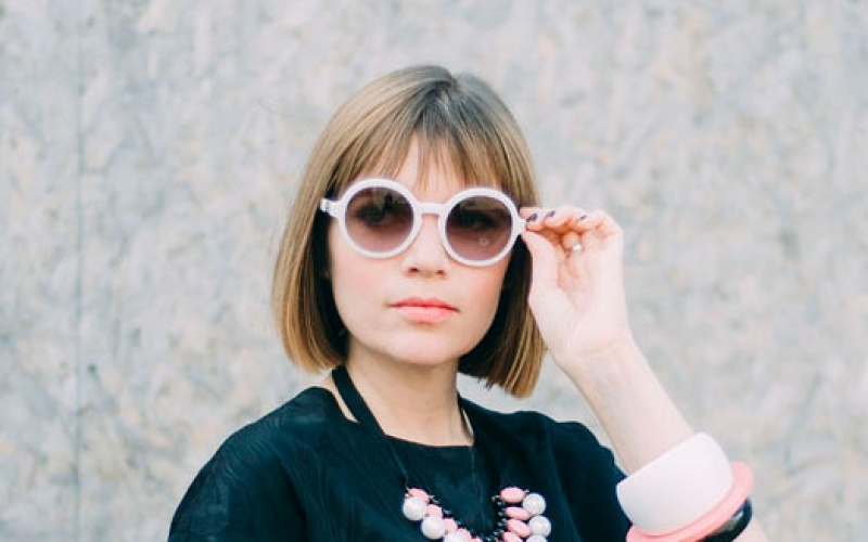 photo of alum Kate Cooper standing and looking away from camera with hand holding rose tinted sunglasses and hair in a short bob wearing a loose short sleeved top with a necklace and large bracelet against faint floral background