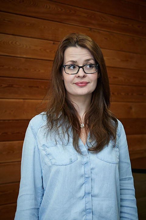 portrait photo of lecturer Katy White standing and looking away from camera with long brown hair and black glasses and light blue denim shirt